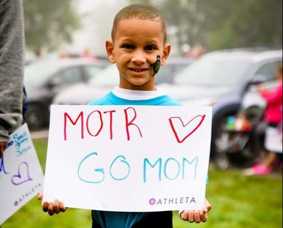 Young boy cheering at Moms on the Run 5k/10k/Kids Run