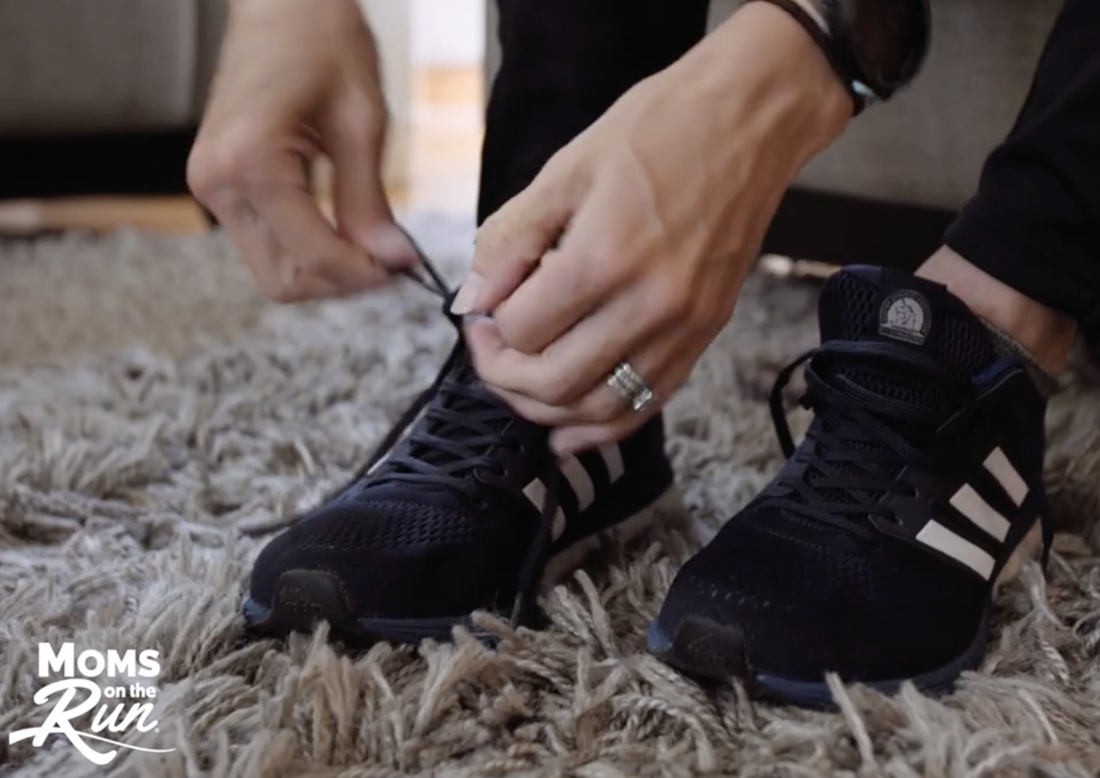 Woman tying pair of black running shoes